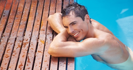 Happy attractive man resting relaxed on edge of swimming pool photo