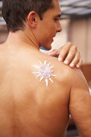 Man having sunscreen in sun shape on his back photo