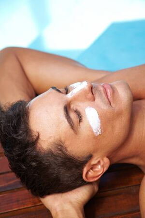 Relaxed man sunbathing with sunscreen on his nose and cheeks photo