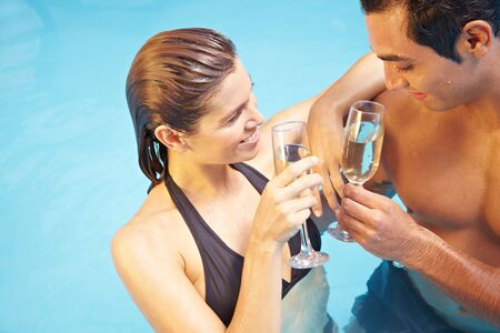 Man and woman drinking together glass of champagne in swimming pool photo