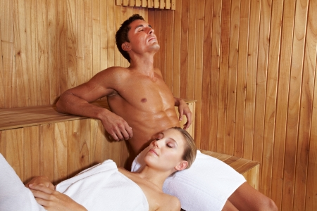 Relaxed attractive couple enjoying peace in sauna photo