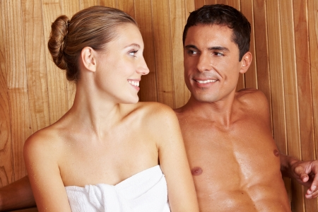 Attractive young couple in sauna looking at each other and smiling photo
