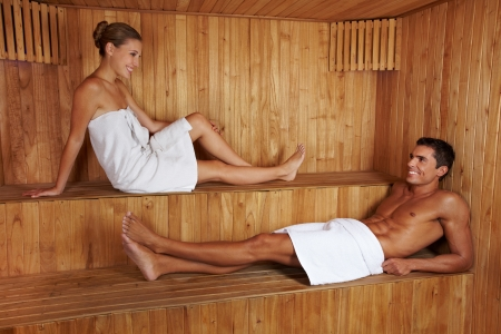 Attractive man and young woman talking to each other in sauna photo