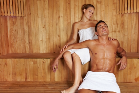 sauna: Attractive man and beautiful woman relaxing together in sauna