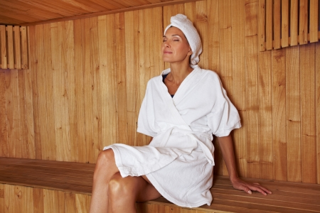 Senior woman sitting relaxed in wooden sauna photo