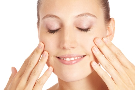 Smiling attractive woman applying moisturizer lotion to her face photo