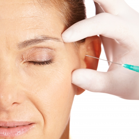 injection woman: Elderly woman getting her eye wrinkles and crows feet removed Stock Photo