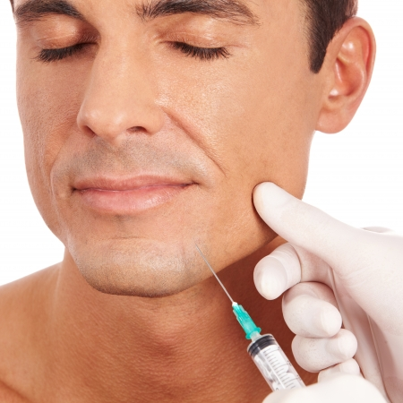 chin on hands: Attractive man at plastic surgery with syringe in his face