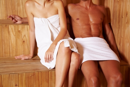 advances: Anonymous couple sitting next to each other in sauna
