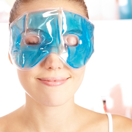 cool girl: Attractive young woman enjoying cooling eye gel mask in her face