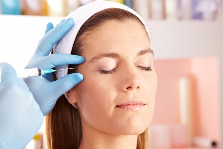 beauty treatment clinic: Woman in beauty clinic getting botox injection to remove eye wrinkles Stock Photo
