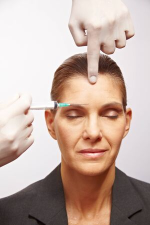 injected: Senior woman getting a syringe injected at plastic surgery