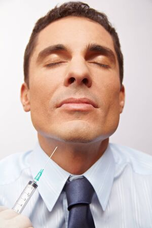 attractiveness: Business man getting needle in chin at cosmetic surgery