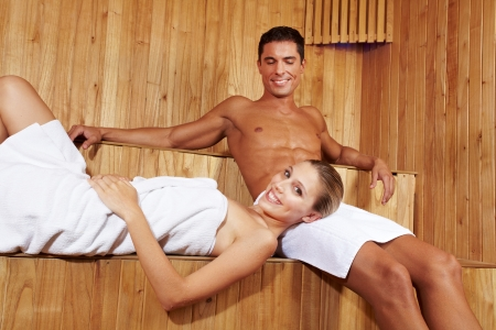 Happy smiling couple relaxing together in a sauna photo