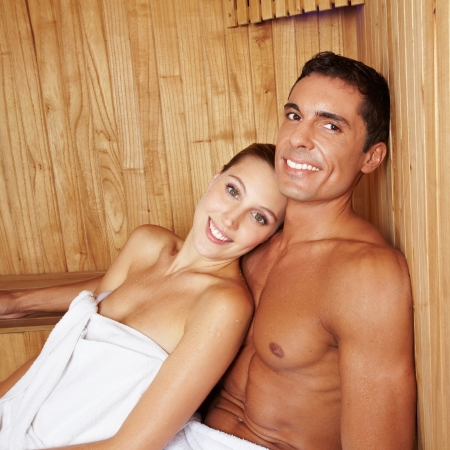 Attractive happy couple relaxing together in a sauna photo