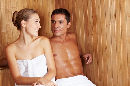 Happy woman and man sitting together in a sauna photo