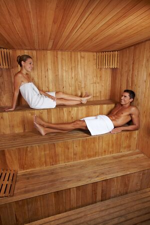 Happy man and woman sitting together in a wooden sauna photo