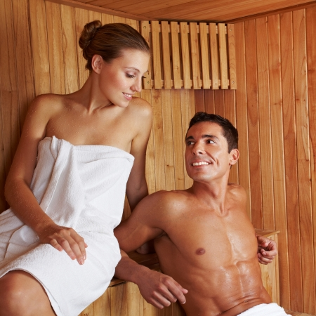 Beautiful young couple sitting together in a sauna photo