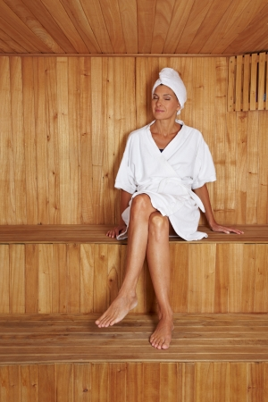 Elderly woman sitting relaxed in a sauna photo