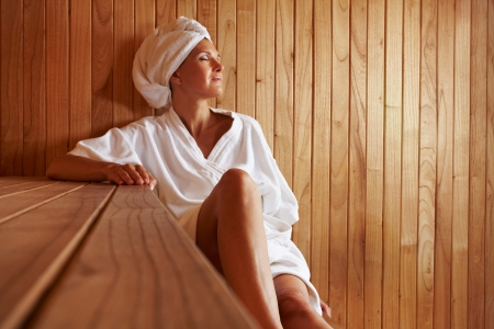 spa treatment: Elderly woman sitting relaxed in a wooden sauna