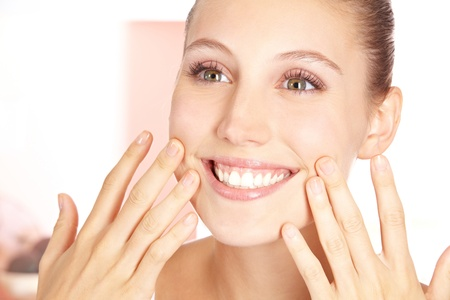 Smiling happy woman feeling her pure skin with her fingers photo