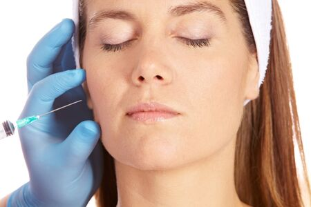 feminine beauty: Elderly woman getting wrinkles removed in her cheeks with syringe