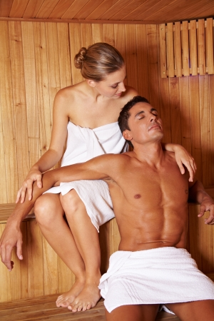 Attractive relaxed couple enjoying a sauna treatment together photo