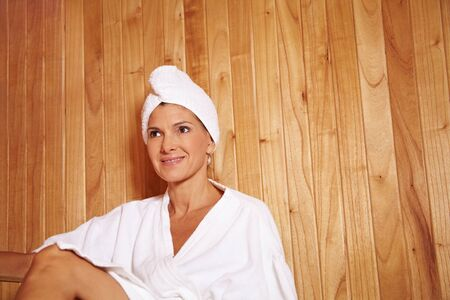 Elderly woman sitting relaxed in a sauna in a health resort photo