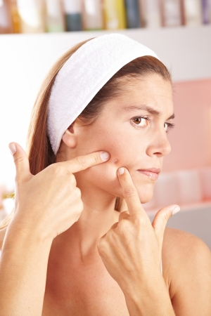 squeezing: Woman in bathroom squeezing pimple on her cheek