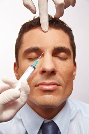 injection: Attractive manager getting needle in forehead for wrinkle removal