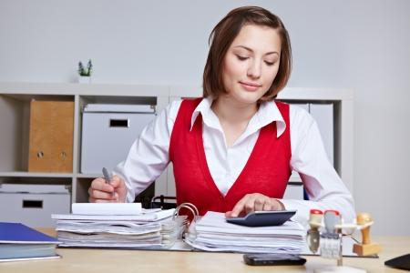 auditor�a: Mujer de negocios haciendo una inspecci�n fiscal en la oficina con los archivos y la calculadora Foto de archivo