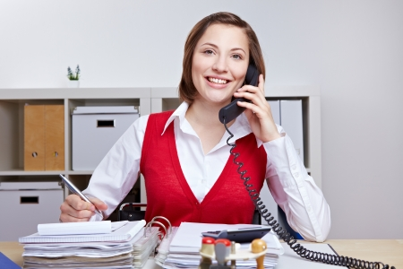 Happy attractive business woman using her phone in office for a call 版權商用圖片