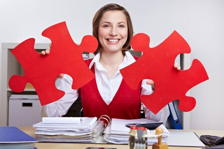 Smiling woman with two oversized red jigsaw puzzle pieces photo