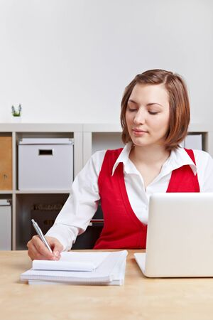 Businesswoman with computer taking notes at her desk in the office Stock Photo - 13934220