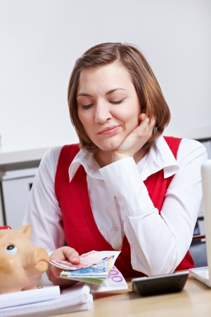 Frustrated woman looking at Euro money in office photo
