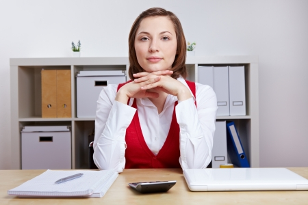 Portrait of an attractive business woman sitting at her desk in the office photo