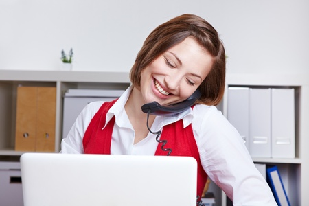 Woman making a phone call while working with a laptop computer in the office photo