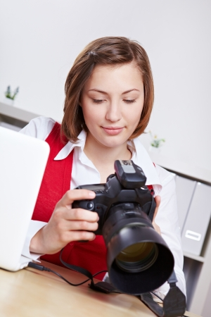 Female photographer in studio checking images on DSLR camera display photo