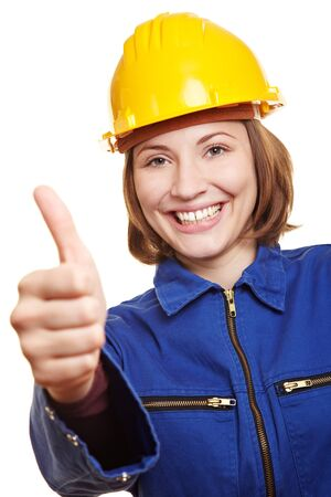 boiler suit: Cheering happy craftswoman in blue boiler suit holding thumbs up