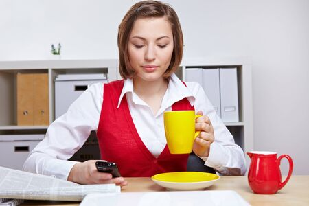 Woman in office taking a break with cup of coffee and smartphone photo