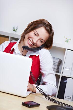 centro de computo: Sonriente femenino de los estudios en el escritorio con computadora portátil usando el teléfono Foto de archivo