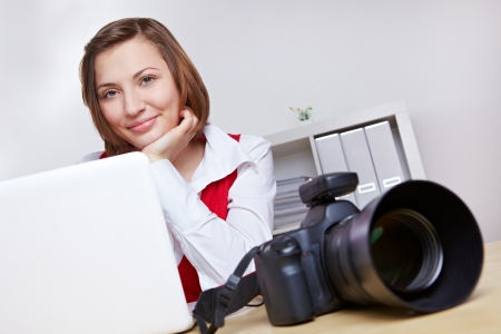 Happy female photographer in studio with camera and laptop computer photo