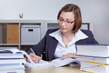 Business woman at her desk in the office doing research with books photo