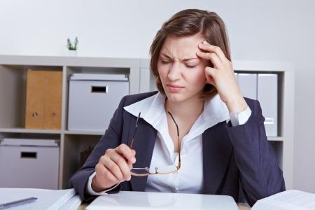 pangs: Business donna seduta con mal di testa alla sua scrivania in ufficio Archivio Fotografico