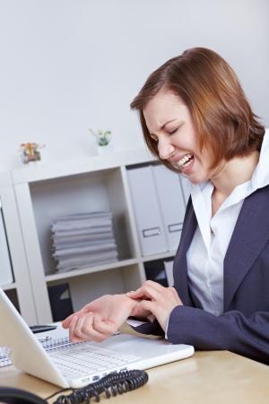 pangs: Donna con il computer in ufficio con l'artrite al polso mano