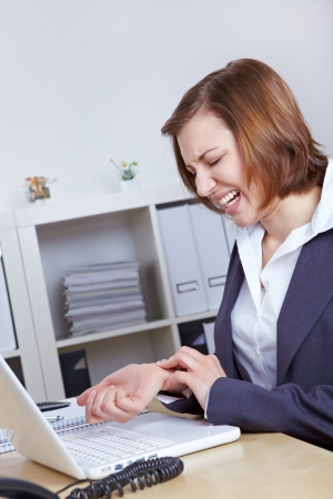 Woman with computer in office with arthritis in her hand wrist photo