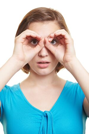 imitations: Curious woman looking through her fingers in front of her eyes Stock Photo