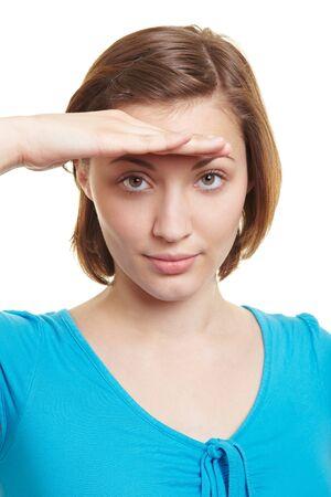 descubridor: Mujer atractiva que busca en la distancia con la mano sobre los ojos