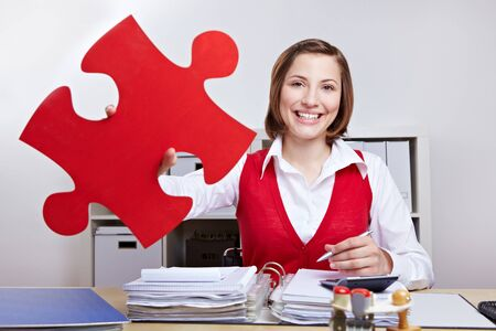 Attractive businesswoman holding oversized red jigsaw puzzle piece photo