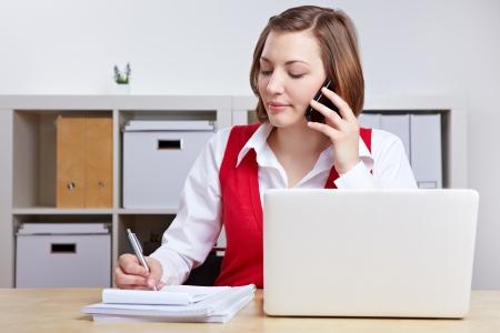 llamando: Mujer que trabaja en el escritorio con ordenador portátil y teléfono móvil